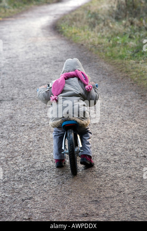 Young child biking down a asphalt path in wintertime - Stock Photo