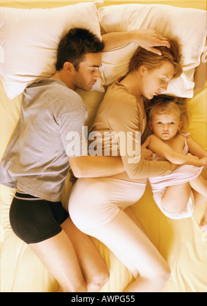 Man, pregnant woman and child lying in bed, elevated view - Stock Photo