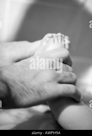 Father's hand holding baby's feet, close-up, b&w - Stock Photo