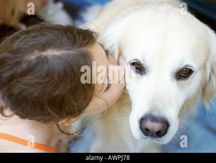 Girl kissing dog, elevated view - Stock Photo