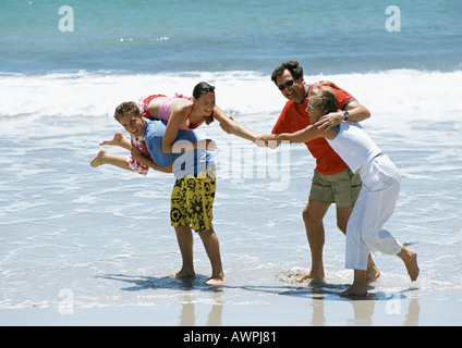 Family playing together at the beach. - Stock Photo