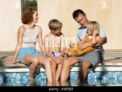 Young family sitting together, feet in pool (frontal view). - Stock Photo