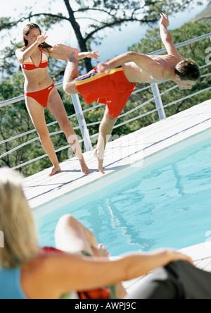 Woman watching teenage girl push teenage boy into pool. - Stock Photo