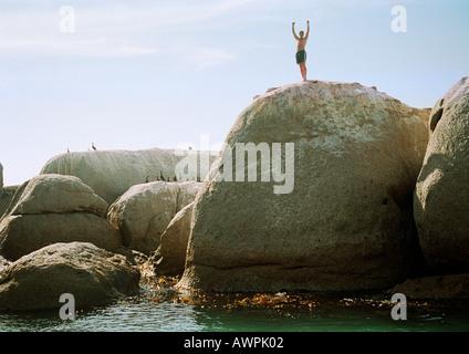 Man standing on rock overlooking sea - Stock Photo