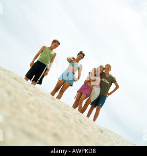 Teenagers in bathing suits standing on sand, low angle view - Stock Photo