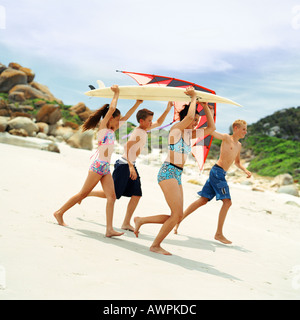 Teenagers and children in swimsuits holding surfboard and kite - Stock Photo