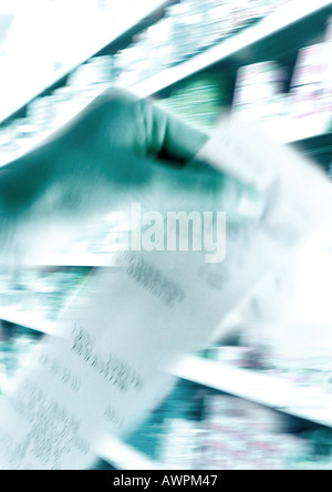 Hand holding receipt, shelves in background, blurred - Stock Photo