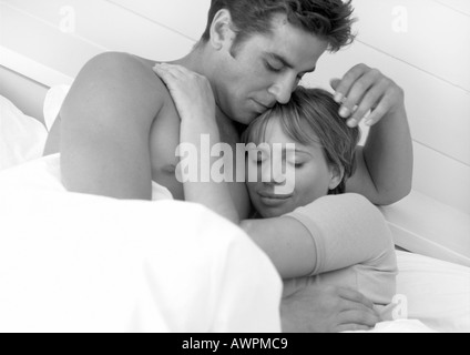 Couple hugging in bed, b&w - Stock Photo
