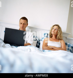 Couple in bed, man using laptop computer, woman with arms crossed - Stock Photo