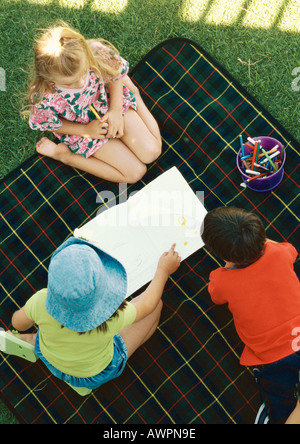 Three children kneeling on blanket outside, elevated view - Stock Photo