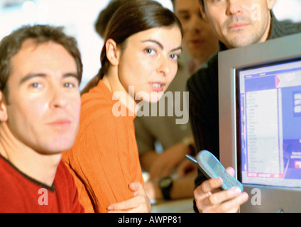 Adults grouped around computer screen, close-up, looking at camera - Stock Photo