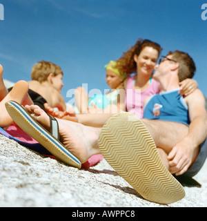 Couple and children on beach, focus on man's feet in foreground - Stock Photo