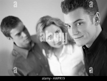 Woman standing between two men, b&w - Stock Photo