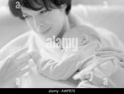 Mother holding sleeping infant on chest, b&w - Stock Photo