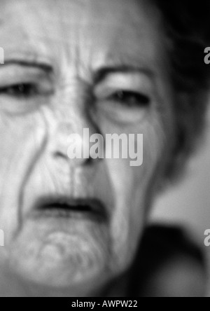 Senior woman frowning, close-up, portrait, b&w - Stock Photo