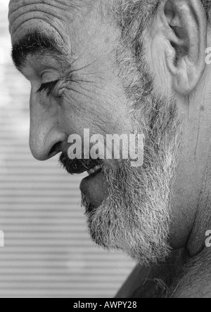 Mature man smiling, side view, close-up, b&w. - Stock Photo