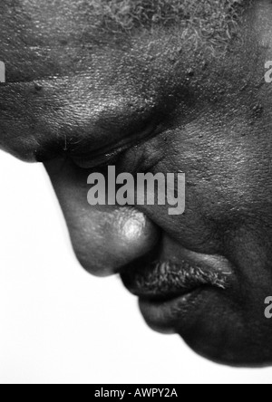 Senior man looking down, close-up, b&w. - Stock Photo