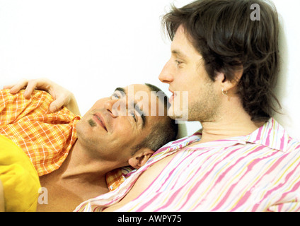 Two men, one with arm around the other, portrait. - Stock Photo
