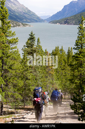 Hikers carrying backpacks on the way to Lake Benett, mountain landscape, Chilkoot Trail, British Columbia, Canada - Stock Photo