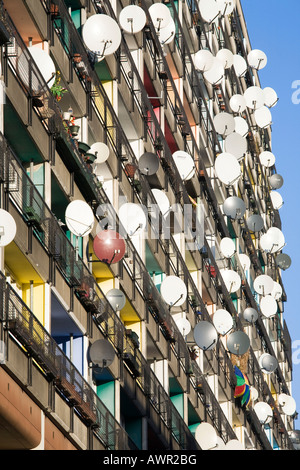Lots of satellite dishes mounted to balconies on an apartment building facade, Pallasseum or 'Berlin Social Palace' - Stock Photo