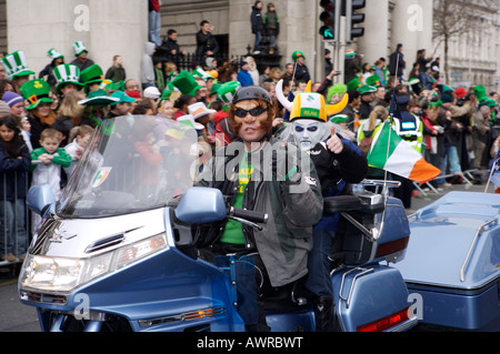 A man and boy wearing masks on a large motorcycle in the St. Patrick's Day Parade in Dublin Ireland - Stock Photo