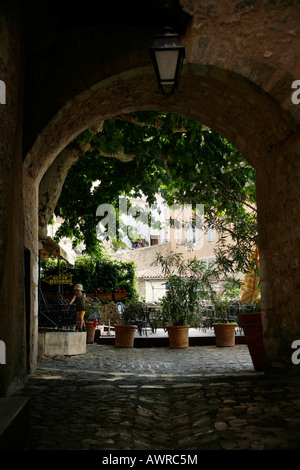 A child plays in an archway, Moustiers-Sainte-Marie, Alpes-de-Haute-Provence, France - Stock Photo