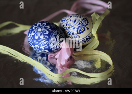 two blue and white traditional handpainted Czech eggs are encircled by pink and yellow ribbon and reflect on silver - Stock Photo