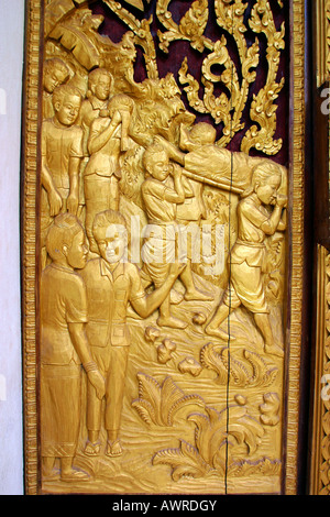 Laos Vientiane Wat That Fun carved wooden window mourning scene - Stock Photo
