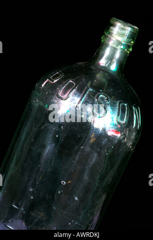 a large poison toxins toxic bottle with poisonous written in relief on the outside clear empty shot against a black - Stock Photo