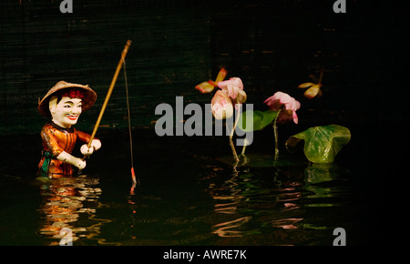 A FISHERMAN and LOTUS FLOWERS inside the THANG LONG WATER PUPPET THEATRE HANOI VIETNAM - Stock Photo