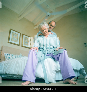 Mature man massaging woman, low angle view - Stock Photo