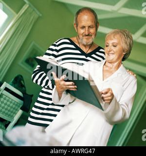 Mature man and woman looking at book - Stock Photo