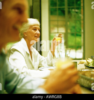 Mature woman sitting at table, holding glass, man blurred in foreground - Stock Photo