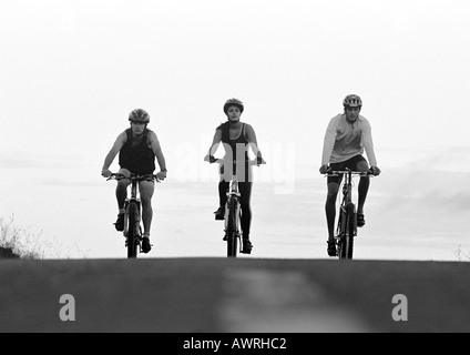 Two men, one woman, cycling on path, b&w.