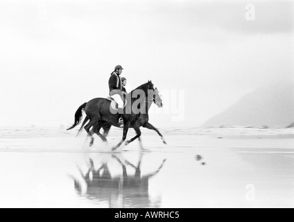 Two people riding horses on beach, side view, b&w.