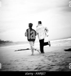 Mature couple running on beach, rear view, b&w - Stock Photo