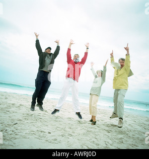 Mature group on beach, jumping in air, looking into camera - Stock Photo