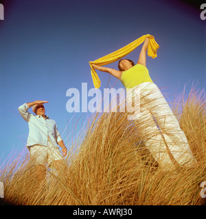 Mature couple standing in tall grass, woman holding scarf above head - Stock Photo