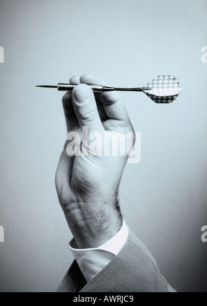 Hand holding dart, close-up - Stock Photo