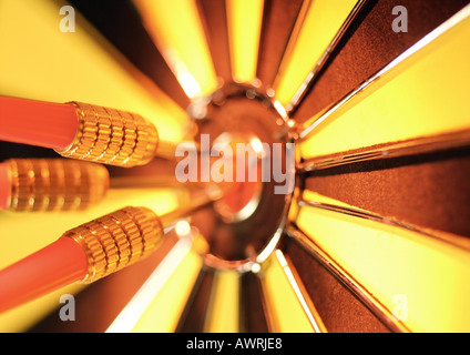Darts in bullseye of dartboard, close-up - Stock Photo