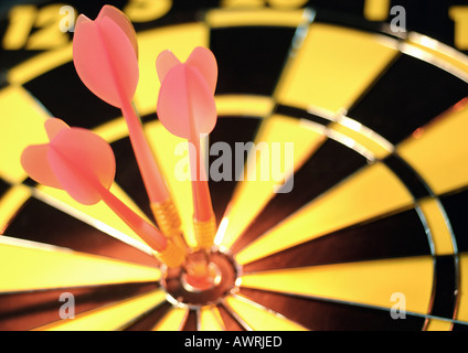 Darts in bull's-eye of dartboard, close-up - Stock Photo