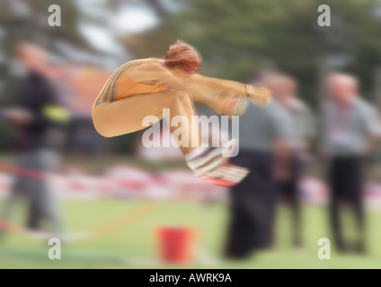 Female long jumper in mid-air, blurred motion - Stock Photo