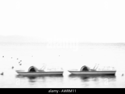 Paddle boats in water, defocused, b&w. - Stock Photo