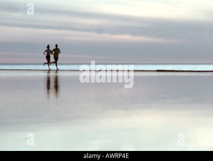Couple running on beach - Stock Photo