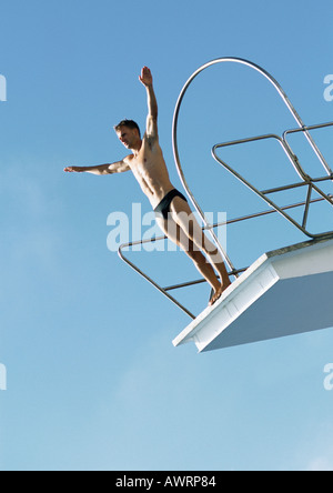 Man preparing to dive from diving board, low angle view - Stock Photo