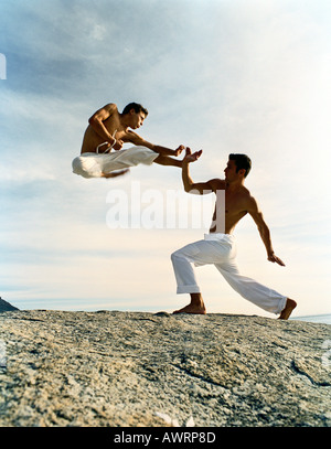 Two men performing martial arts on rocky ground, one in mid-air, full length - Stock Photo
