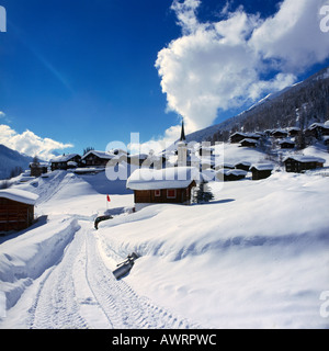 Tyre tracks in heavy winter snow along a road with chalets and church beyond in Biel village The Goms Valley Switzerland - Stock Photo