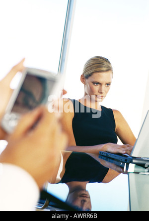 Businesswoman using computer, hands holding pocket computer - Stock Photo