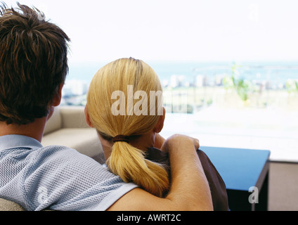 Man with arm on woman's shoulder, rear view, close-up - Stock Photo