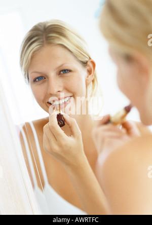 Woman putting on lipstick in mirror, portrait - Stock Photo